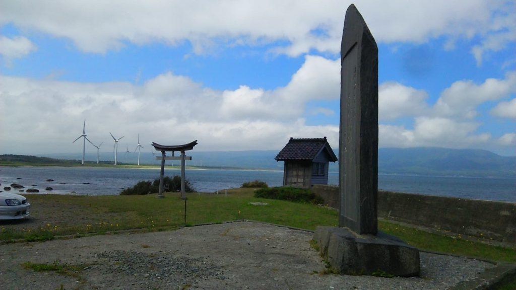 小西正尚撮影の江差追分歌碑と遠くに見える風力発電