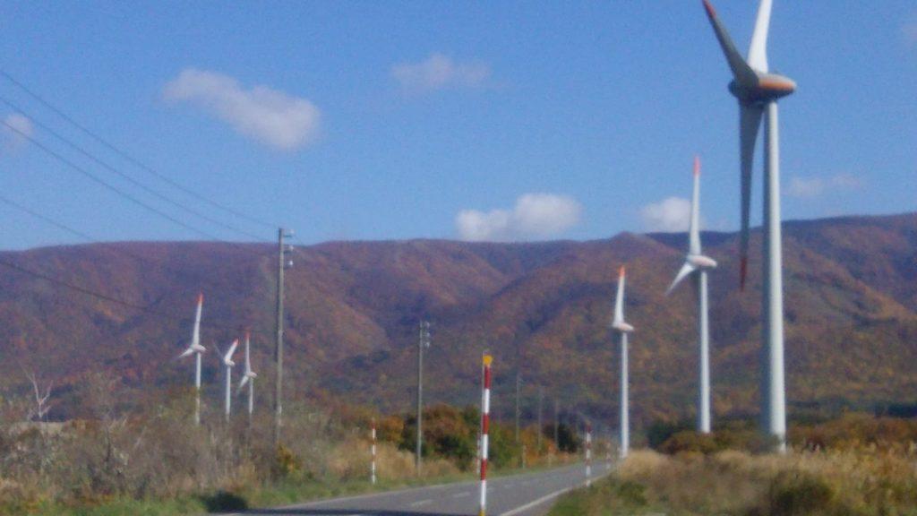 小西正尚が撮影した寿都町の風車の写真。美しく紅葉した山を背景に、大きな風車が立ち並ぶ。